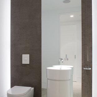 Modelo de aseo contemporáneo con sanitario de pared y lavabo con pedestal