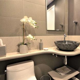 Выдающиеся фото от архитекторов и дизайнеров интерьера: маленький туалет в стиле модернизм с унитазом-моноблоком, коричневой плиткой, керамогранитной плиткой, фиолетовыми стенами, полом из керамогранита, настольной раковиной, столешницей из искусственного кварца и серым полом