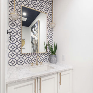 Cette photo montre un WC et toilettes chic de taille moyenne avec un placard à porte shaker, des portes de placard blanches, un WC séparé, un carrelage bleu, un mur blanc, un sol en marbre, un lavabo encastré, un sol blanc, un plan de toilette blanc, meuble-lavabo suspendu et un plafond en papier peint.
