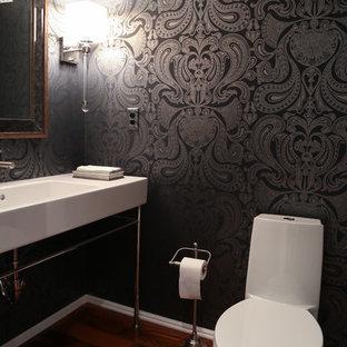 Стильный дизайн: туалет среднего размера в современном стиле с унитазом-моноблоком, белой плиткой, плиткой из листового камня, черными стенами, паркетным полом среднего тона и раковиной с несколькими смесителями - последний тренд