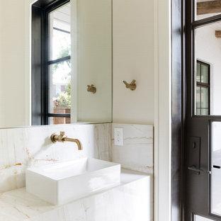 Cette photo montre un WC et toilettes chic avec du carrelage en marbre, une vasque, un plan de toilette en marbre, un carrelage beige, un mur beige et un plan de toilette beige.