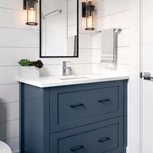 バンクーバーの小さいカントリー風おしゃれなトイレ・洗面所 (シェーカースタイル扉のキャビネット、青いキャビネット、白いタイル、セラミックタイル、セメントタイルの床、クオーツストーンの洗面台、白い洗面カウンター、一体型トイレ、アンダーカウンター洗面器) の写真