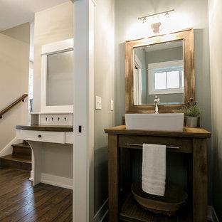 На фото: маленькие туалеты в стиле кантри с открытыми фасадами, искусственно-состаренными фасадами, раздельным унитазом, полом из ламината, настольной раковиной, столешницей из дерева, коричневым полом и серыми стенами