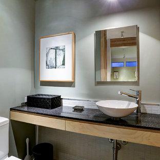 Стильный дизайн: маленький туалет в стиле модернизм с плоскими фасадами, светлыми деревянными фасадами, раздельным унитазом, белой плиткой, стеклянной плиткой, зелеными стенами, настольной раковиной, столешницей из искусственного камня и черной столешницей - последний тренд