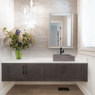 На фото: с высоким бюджетом большие туалеты в стиле фьюжн с фасадами с утопленной филенкой, серыми фасадами, серой плиткой, керамогранитной плиткой, серыми стенами, полом из керамогранита, настольной раковиной, столешницей из искусственного кварца, бежевым полом и белой столешницей
