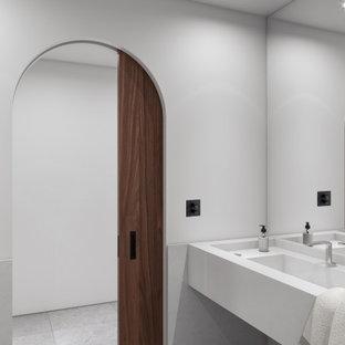 Пример оригинального дизайна: огромный туалет в восточном стиле с белыми фасадами, писсуаром, белой плиткой, мраморной плиткой, белыми стенами, полом из известняка, монолитной раковиной, мраморной столешницей, серым полом и белой столешницей