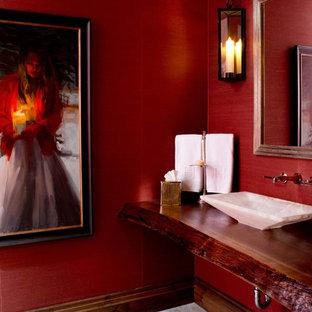 На фото: туалеты в современном стиле с настольной раковиной, столешницей из дерева, красными стенами и красной столешницей