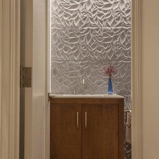 Réalisation d'un petit WC et toilettes design avec un placard à porte plane, des portes de placard en bois brun, un WC séparé, un carrelage blanc, un carrelage de pierre, un mur blanc, un sol en bois foncé, un lavabo encastré, un plan de toilette en quartz modifié, un sol marron et un plan de toilette blanc.
