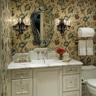 Exemple d'un très grand WC et toilettes chic avec des portes de placard beiges, un WC à poser, un mur multicolore, un sol en marbre, un plan de toilette en marbre, un lavabo encastré, un placard avec porte à panneau encastré et un sol blanc.