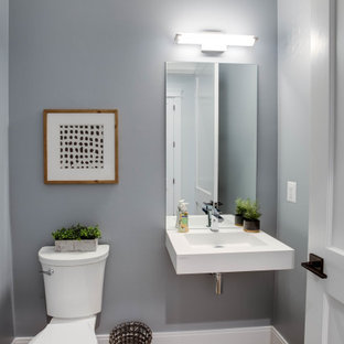 Mid-sized minimalist powder room photo in DC Metro with a two-piece toilet, gray walls, a wall-mount sink and white countertops