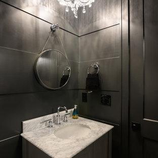Réalisation d'un WC et toilettes champêtre de taille moyenne avec un placard en trompe-l'oeil, des portes de placard grises, un WC séparé, un mur noir, un sol en bois clair, un lavabo encastré, un plan de toilette en marbre, un sol gris et un plan de toilette blanc.
