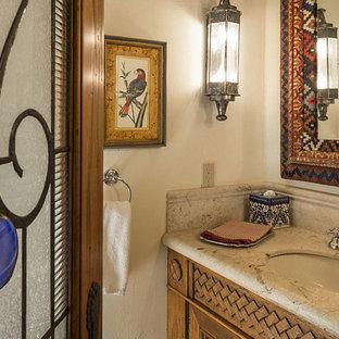Idee per un bagno di servizio mediterraneo di medie dimensioni con consolle stile comò, ante in legno scuro, pareti beige, lavabo sottopiano e top in pietra calcarea