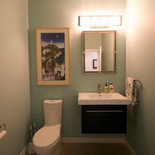 Пример оригинального дизайна: туалет среднего размера в стиле модернизм с монолитной раковиной, плоскими фасадами, темными деревянными фасадами, раздельным унитазом, серой плиткой, синими стенами и полом из керамической плитки