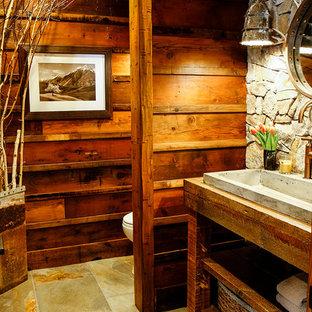 Exemple d'un WC et toilettes montagne de taille moyenne avec un carrelage gris, un carrelage de pierre, un mur marron, un sol en ardoise, un plan de toilette en bois et un plan de toilette marron.