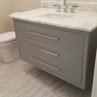 Пример оригинального дизайна: туалет среднего размера в стиле модернизм с плоскими фасадами, серыми фасадами, раздельным унитазом, бежевыми стенами, полом из керамогранита, врезной раковиной, столешницей из талькохлорита, серым полом и белой столешницей