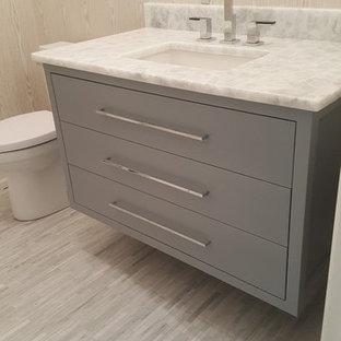 Cette photo montre un WC et toilettes moderne de taille moyenne avec un placard à porte plane, des portes de placard grises, un WC séparé, un mur beige, un sol en carrelage de porcelaine, un lavabo encastré, un plan de toilette en stéatite, un sol gris et un plan de toilette blanc.