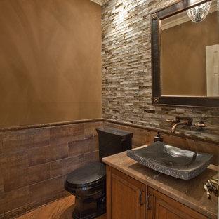 На фото: туалет в классическом стиле с настольной раковиной, фасадами с выступающей филенкой, фасадами цвета дерева среднего тона, столешницей из травертина, раздельным унитазом и коричневой плиткой