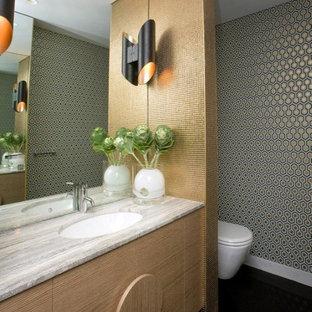 Idée de décoration pour un WC et toilettes vintage de taille moyenne avec un lavabo encastré, des portes de placard en bois clair et un mur multicolore.