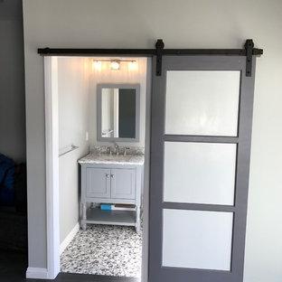 ロサンゼルスの中くらいのトランジショナルスタイルのおしゃれなトイレ・洗面所 (シェーカースタイル扉のキャビネット、グレーのキャビネット、分離型トイレ、グレーのタイル、白い壁、玉石タイル、アンダーカウンター洗面器、大理石の洗面台、マルチカラーの床、グレーの洗面カウンター) の写真