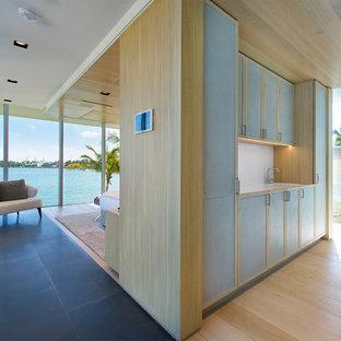 Immagine di un ampio bagno di servizio minimal con ante lisce, ante blu, parquet chiaro, lavabo integrato, pavimento beige, top bianco e top in acciaio inossidabile