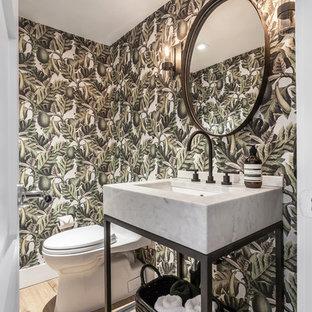 Modelo de aseo contemporáneo, pequeño, con puertas de armario blancas, sanitario de una pieza, paredes verdes, suelo laminado, suelo beige, encimeras blancas, armarios abiertos y lavabo tipo consola
