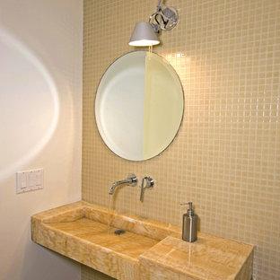 Пример оригинального дизайна: туалет среднего размера в стиле модернизм с желтой плиткой, монолитной раковиной, столешницей из оникса и плиткой мозаикой