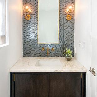 Idéer för funkis toaletter, med släta luckor, skåp i mörkt trä, grå kakel, vita väggar, ljust trägolv, ett undermonterad handfat och beiget golv