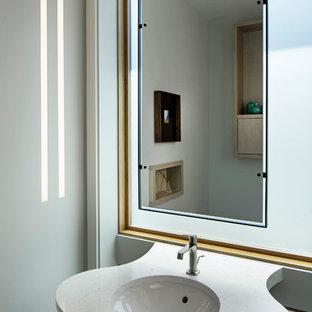 ロサンゼルスの小さいコンテンポラリースタイルのおしゃれなトイレ・洗面所 (フラットパネル扉のキャビネット、淡色木目調キャビネット、壁掛け式トイレ、磁器タイルの床、アンダーカウンター洗面器、クオーツストーンの洗面台、白い洗面カウンター) の写真