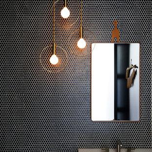 Imagen de aseo contemporáneo con baldosas y/o azulejos negros, baldosas y/o azulejos en mosaico, paredes negras, lavabo bajoencimera, puertas de armario de madera oscura y encimeras blancas