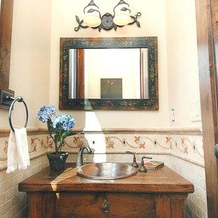 Inspiration pour un petit WC et toilettes méditerranéen avec un placard à porte plane, des portes de placard en bois brun, un carrelage beige, des carreaux en terre cuite, un mur beige, un plan de toilette en bois et un plan de toilette marron.
