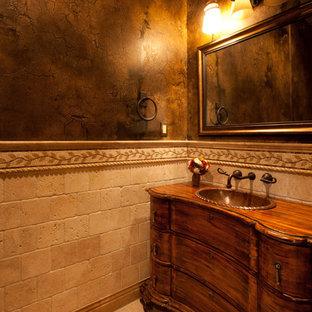 Пример оригинального дизайна интерьера: маленький туалет в средиземноморском стиле с фасадами островного типа, фасадами цвета дерева среднего тона, бежевой плиткой, терракотовой плиткой, коричневыми стенами, мраморным полом, накладной раковиной, столешницей из дерева, бежевым полом и коричневой столешницей