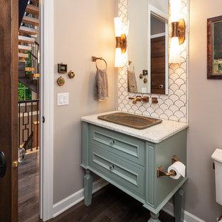 Cette image montre un WC et toilettes traditionnel avec un placard avec porte à panneau encastré, des portes de placard turquoises, un carrelage blanc, un mur gris, un sol en bois foncé, un lavabo posé, un sol marron et un plan de toilette blanc.
