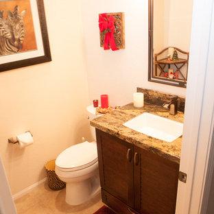 Immagine di un bagno di servizio classico di medie dimensioni con ante a persiana, ante in legno scuro, pareti beige, pavimento in gres porcellanato, lavabo sottopiano, top in granito e pavimento beige