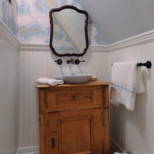 Immagine di un piccolo bagno di servizio vittoriano con lavabo a bacinella, ante in legno scuro, top in legno, pavimento con piastrelle a mosaico, ante con riquadro incassato e top marrone