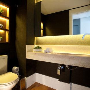 На фото: маленький туалет в современном стиле с коричневыми стенами, светлым паркетным полом, монолитной раковиной и столешницей из травертина с