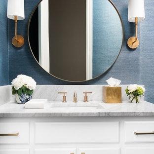 Imagen de aseo tradicional renovado con armarios con paneles con relieve, puertas de armario blancas, paredes azules, lavabo bajoencimera, encimera de mármol y encimeras grises