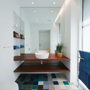 Cette image montre un WC et toilettes nordique de taille moyenne avec une vasque, un plan de toilette en bois, un mur blanc, un placard sans porte, des portes de placard en bois sombre, un carrelage multicolore, un sol en carrelage de céramique, un sol multicolore et un plan de toilette marron.