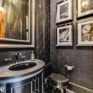 オースティンの地中海スタイルのおしゃれなトイレ・洗面所 (家具調キャビネット、黒いキャビネット、一体型トイレ、黒い壁、大理石の床、アンダーカウンター洗面器、ソープストーンの洗面台、マルチカラーの床) の写真