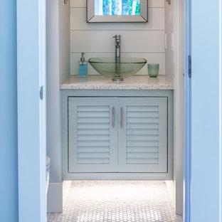 На фото: маленькие туалеты в морском стиле с фасадами с филенкой типа жалюзи, полом из мозаичной плитки, настольной раковиной, столешницей из переработанного стекла и белым полом