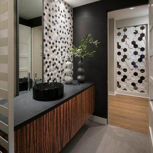Идея дизайна: туалет в современном стиле с фасадами цвета дерева среднего тона, черными стенами, настольной раковиной, серым полом и черной столешницей