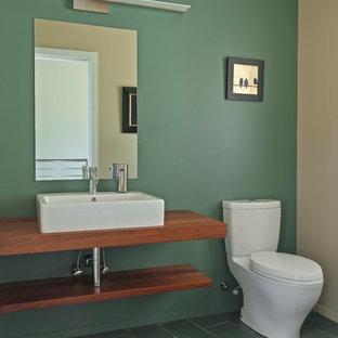 Пример оригинального дизайна: туалет среднего размера в стиле модернизм с фасадами с выступающей филенкой, фасадами цвета дерева среднего тона, раздельным унитазом, зелеными стенами, полом из сланца, настольной раковиной и столешницей из дерева