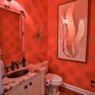 Modelo de aseo de estilo zen, de tamaño medio, con armarios estilo shaker, puertas de armario beige, sanitario de dos piezas, paredes rojas, suelo de madera en tonos medios, lavabo bajoencimera, encimera de granito y suelo marrón