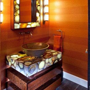 Immagine di un ampio bagno di servizio minimal con consolle stile comò, ante in legno scuro, WC monopezzo, pareti arancioni, pavimento in gres porcellanato, lavabo a bacinella, top in onice, pavimento multicolore e top multicolore