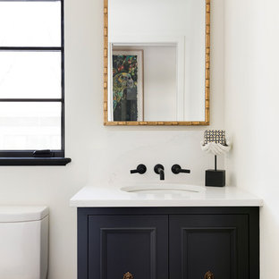 Photo of a small mediterranean cloakroom in Minneapolis with black cabinets, white walls, engineered stone worktops, white worktops, recessed-panel cabinets, a one-piece toilet and a submerged sink.