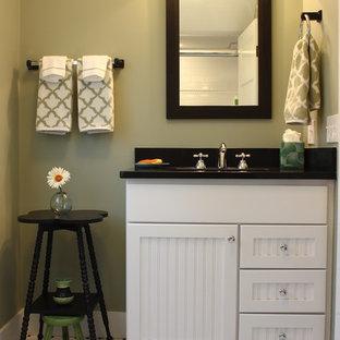 Idée de décoration pour un WC et toilettes champêtre de taille moyenne avec un placard à porte shaker, des portes de placard blanches, un carrelage noir, un carrelage blanc, des carreaux de porcelaine, un mur vert, un sol en carrelage de porcelaine, un lavabo encastré et un plan de toilette en surface solide.