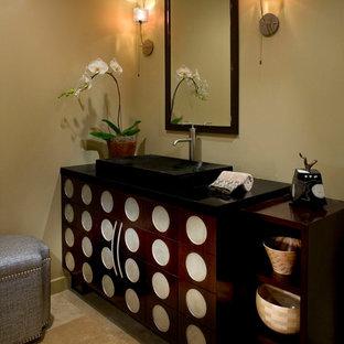 Exemple d'un WC et toilettes chic de taille moyenne avec une vasque, des portes de placard en bois sombre, un carrelage beige, un placard en trompe-l'oeil, un plan de toilette en granite, un mur beige et un sol en travertin.
