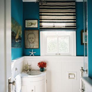 Inspiration pour un WC et toilettes bohème avec un lavabo encastré, un placard avec porte à panneau encastré et des portes de placard blanches.