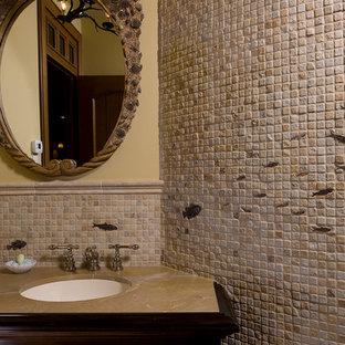 Exemple d'un WC et toilettes chic de taille moyenne avec un placard en trompe-l'oeil, des portes de placard en bois sombre, un carrelage beige, du carrelage en travertin, un mur beige, un lavabo encastré et un plan de toilette beige.