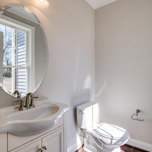 Стильный дизайн: маленький туалет в классическом стиле с фасадами с утопленной филенкой, белыми фасадами, раздельным унитазом, серыми стенами, паркетным полом среднего тона, монолитной раковиной, столешницей из ламината и коричневым полом - последний тренд