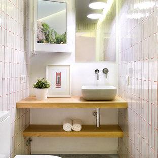 Inredning av ett medelhavsstil litet brun brunt toalett, med öppna hyllor, skåp i mellenmörkt trä, en toalettstol med separat cisternkåpa, rosa kakel, keramikplattor, betonggolv, ett fristående handfat, träbänkskiva och vita väggar